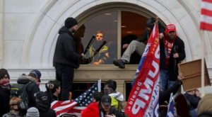 A mob of supporters of Donald Trump climbs through a window as they storm the US Capitol Building in Washington. Source: Reuters