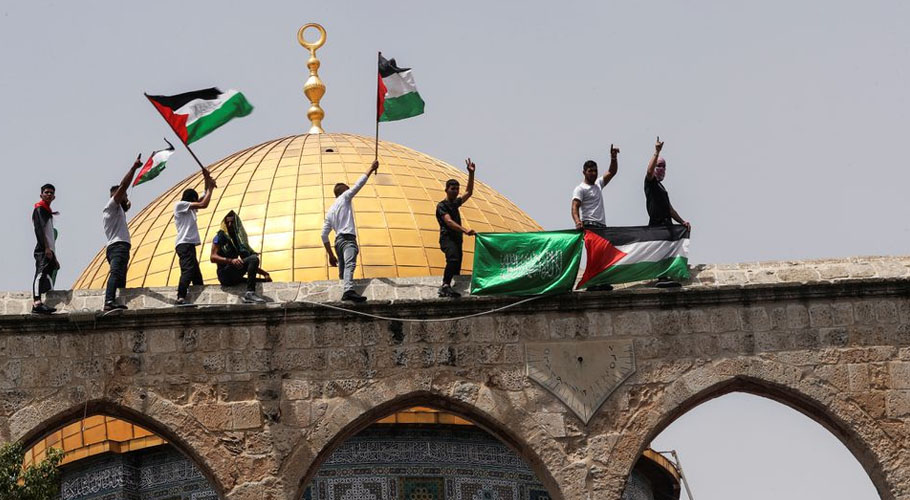 Palestinians hold flags as they stand at the compound that houses Al-Aqsa Mosque. Source: Reuters