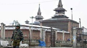 A paramilitary officer patrols in front of the Jamia Masjid in Srinagar