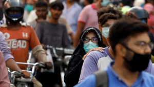 A woman wearing a face mask rides as a passenger on a motorbike amid the coronavirus pandemic. Source: Reuters/VOA
