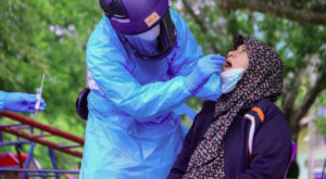 A medical officer conducts a Covid-19 coronavirus test on a woman in southern Thailand. Source: AFP