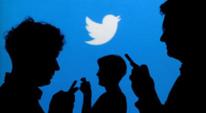 People holding mobile phones are silhouetted against a backdrop projected with the Twitter logo. Source: Reuters.