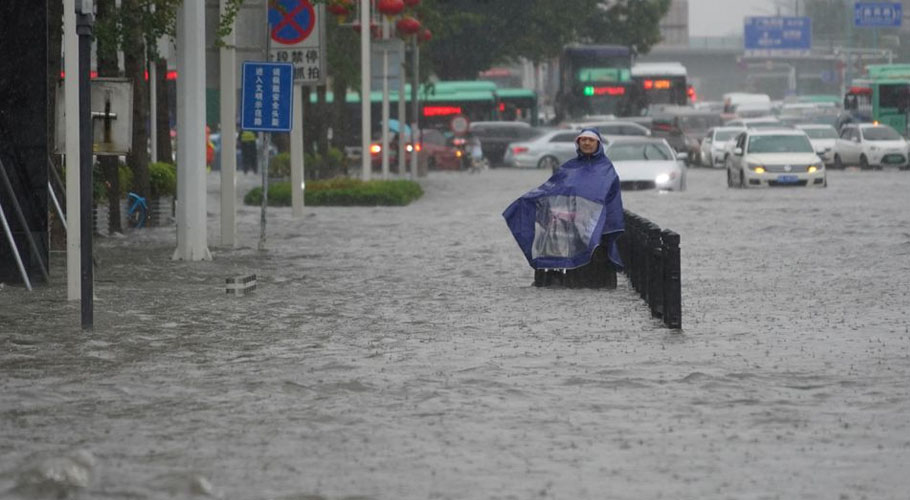 A resident wearing a rain cover stands on a flooded road in Zhengzhou, Henan province: Source Reuters.
