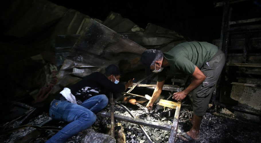 People inspect the damage at the site where a fire broke out at a coronavirus hospital. Source: Reuters.