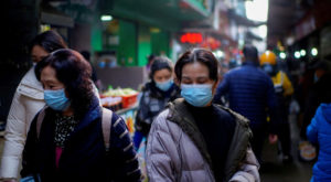 People wearing face masks walk on a street market following an outbreak of Covid-19 in Wuhan. Source: Reuters.